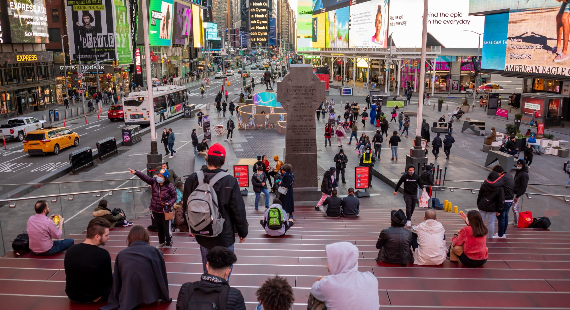 NEW YORK, NEW YORK - MARCH 09: People visit the Red Steps in Times Square amid the coronavirus pandemic on March 09, 2021 in New York City. It has been one year since COVID-19 was first reported in New York City. After undergoing various shutdown orders for the past 12 months, the city is currently in phase 4 of it's reopening plan, allowing for the reopening of low-risk outdoor activities, movie and television productions, indoor dining as well as the opening of movie theaters, all with capacity restrictions. (Photo by Noam Galai/Getty Images)