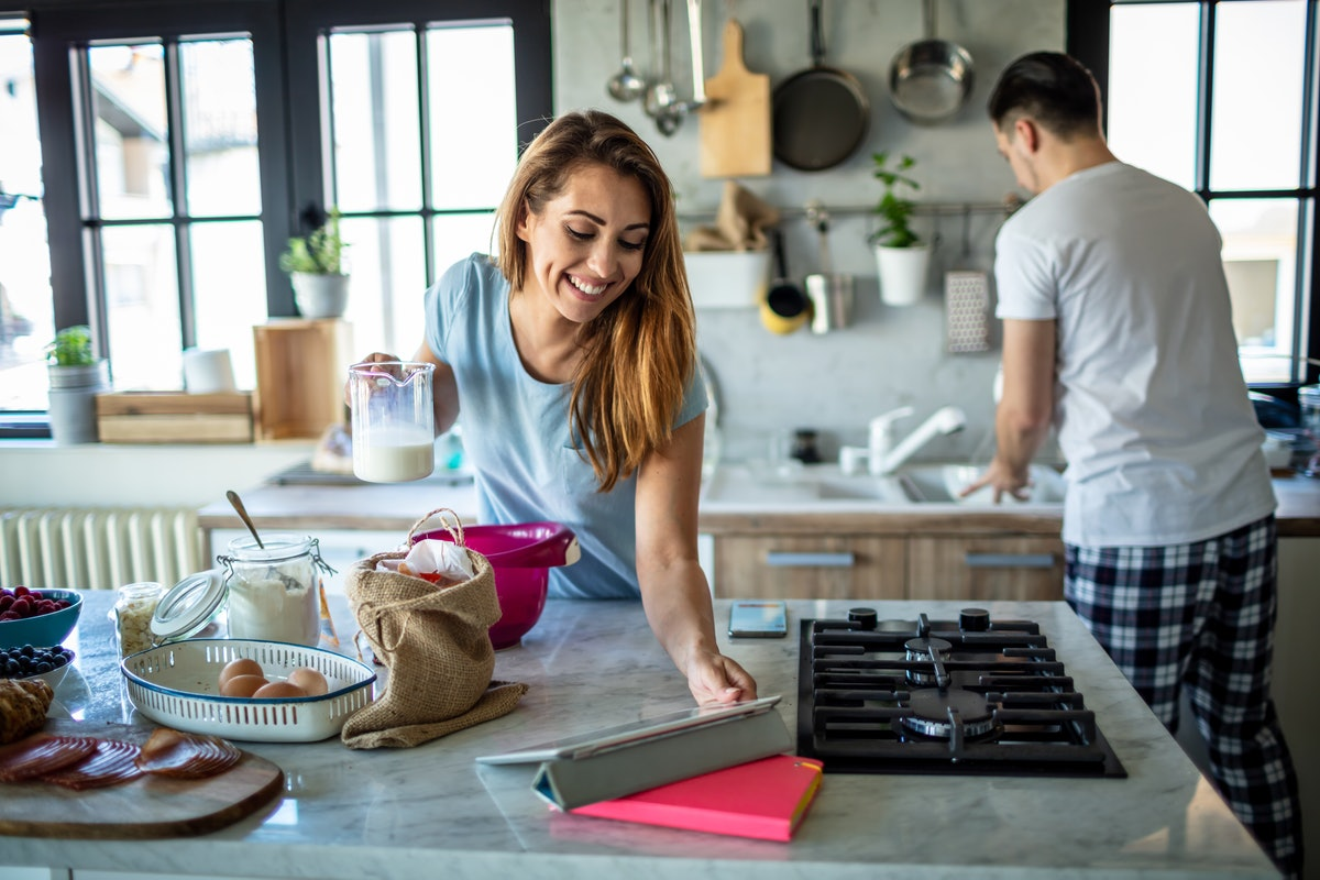A photo of happy couple preparing breakfast in their kitchen with the young woman looking for a reci...