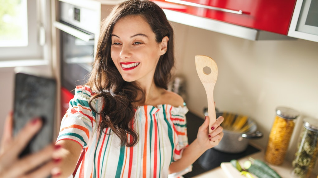 Beautiful young woman using her smart phone and cooking in her kitchen