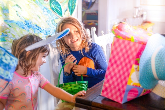 Adorable sisters wearing bunny ears in a candid family photo on Easter morning, they are surrounded by colorful Easter gifts and full of excitement and joy