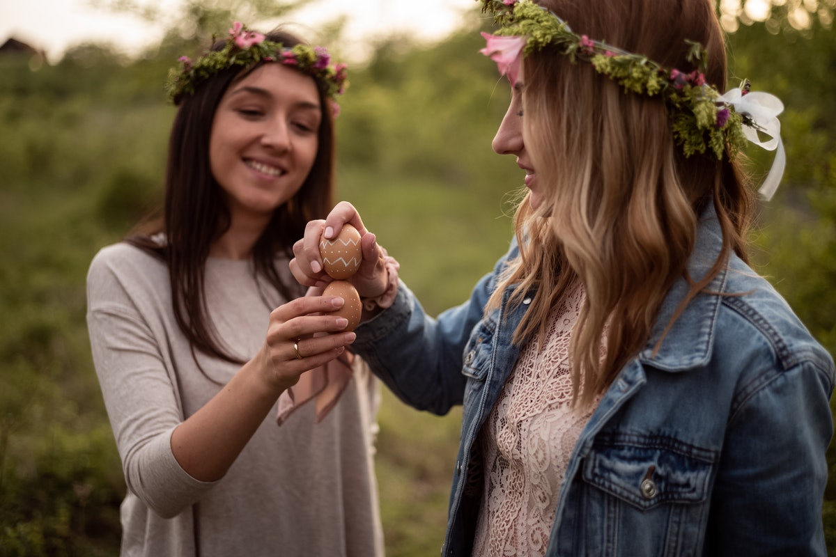 Two female friends with floral crowns breaking easter eggs.