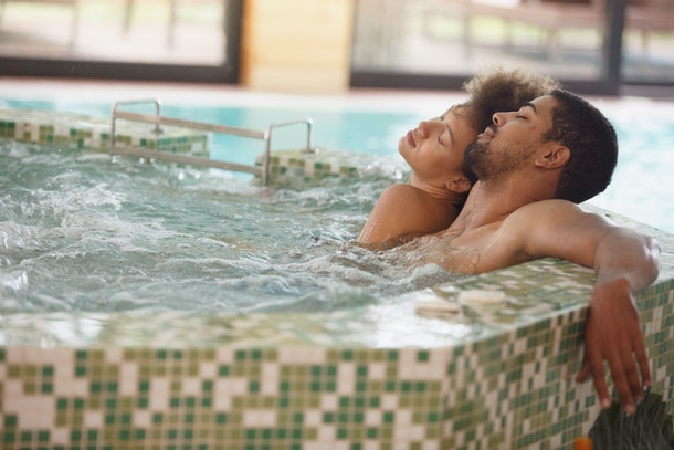 Young couple is having a relaxing bath in a hot tub. They are having a romantic weekend at wellness resort.