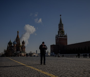 """A man uses his mobile phone on Red Square in downtown Moscow on March 10, 2021. - Russia said on March 10, 2021, it was disrupting Twitter's services because the platform had failed to remove """"illegal"""" content, the latest in a series of moves exerting control over foreign tech giants. The Russian government has been clamping down on sites including Facebook, Twitter and YouTube in recent months for hosting content supporting jailed opposition figure Alexei Navalny. (Photo by Dimitar DILKOFF / AFP) (Photo by DIMITAR DILKOFF/AFP via Getty Images)"""