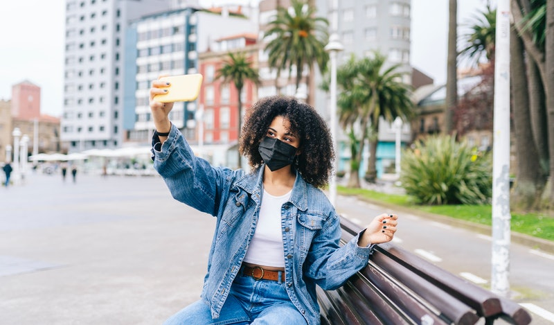 A young girl with afro hair wearing a face mask takes a selfie with the phone in the street. Here's how dispo photo app compares to Instagram