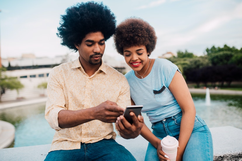 Young African - American couple on vacation sitting in the park and using a smartphone.