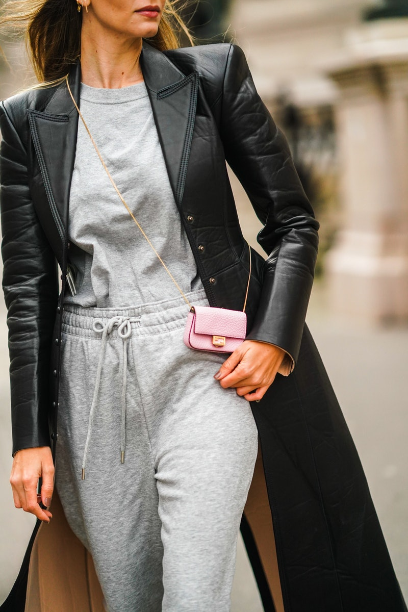 PARIS, FRANCE - FEBRUARY 01: Natalia Verza aka Mascarada wears small circular sunglasses, a black leather long coat with shoulder pads from Fendi, a gray t-shirt, gray sport jogger pants, a pink Fendi mini bag, on February 01, 2021 in Paris, France. (Photo by Edward Berthelot/Getty Images)