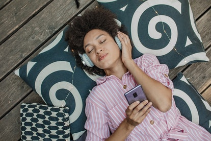 An African woman is at home, listening to music and relaxing, high angle view