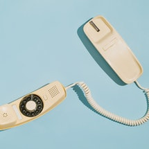 From above of a yellow rotary dial telephone off the hook on a blue background.  Arkansas' latest anti-abortion law will make patients call a hotline before getting an abortion.