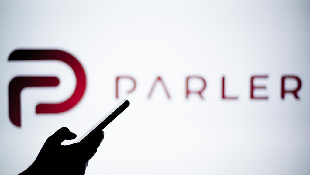SPAIN - 2021/01/14: In this photo illustration a Parler logo is seen behind a smartphone. The 'free speech' social media platform, Parler, a hit with Trump supporters and an alternative to Twitter, stops working after losing support from Amazon, Apple and Google. (Photo Illustration by Thiago Prudêncio/SOPA Images/LightRocket via Getty Images)