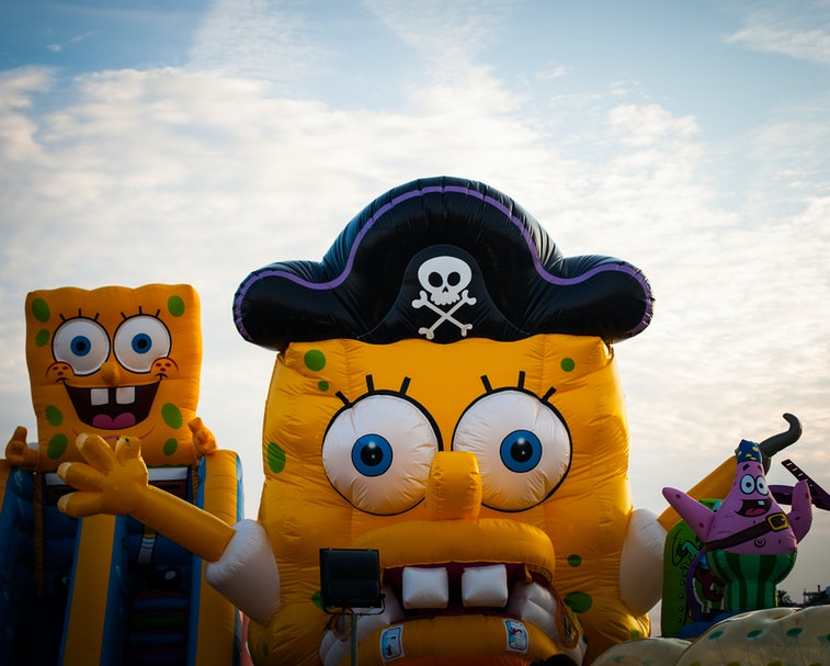 A person is seen wearing a SpongeBob costume with a pirate hat on.