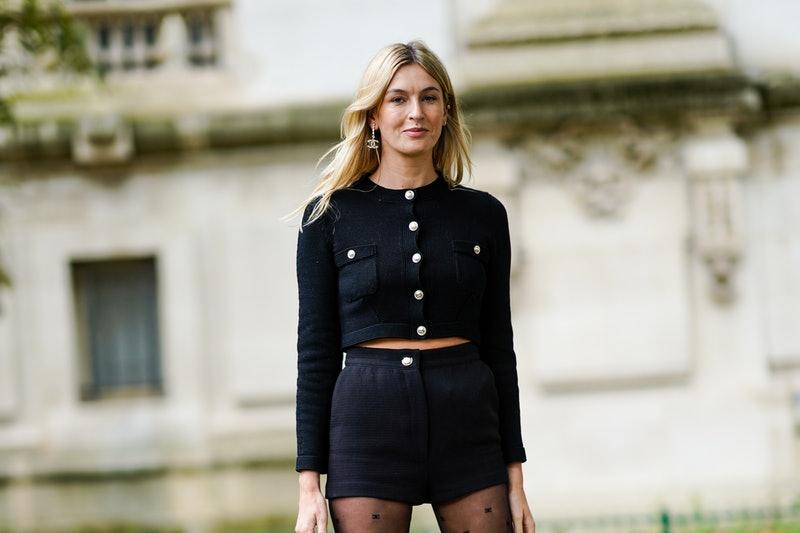 PARIS, FRANCE - OCTOBER 06: Camille Charriere wears a black cardigan with buttons, black shorts, Chanel logo earrings, tights with printed polka dots, outside Chanel, during Paris Fashion Week - Womenswear Spring Summer 2021, on October 06, 2020 in Paris, France. (Photo by Edward Berthelot/Getty Images)