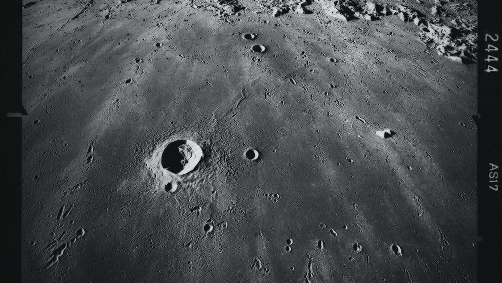 Image of the lunar surface, looking south across Mare Imbrium, with the crater Copernicus (58 miles in diameter) visible in the distance, in an image of the lunar surface taken during the Apollo 17, 7th to 19th December 1972. Crater Pytheas (12 miles in diameter) is visible in the foreground, with several chains of small craters beyond, these are oriented toward Copernicus and are secondary craters produced by material ejected when Copernicus formed. (Photo by Space Frontiers/Archive Photos/Hulton Archive/Getty Images)