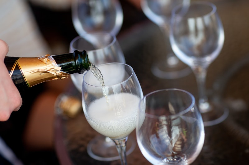 Champagne flutes being filled with champagne