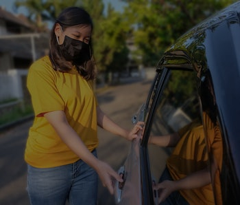 Candid shot of Asian young woman with a protective face mask, opening car door during Covid 19 pandemic. She's standing on the street outside her car.