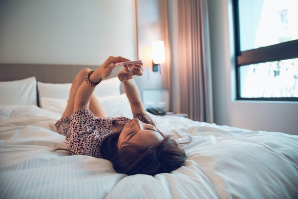 Young Beautiful Woman Using Smart Phone On Bed