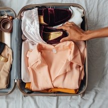 Hands of unrecognisable woman putting velvet loafers in her suitcase. Is it safe to travel once your vaccinated? CDC guidelines for fully vaccinated travel and doctors' advice.