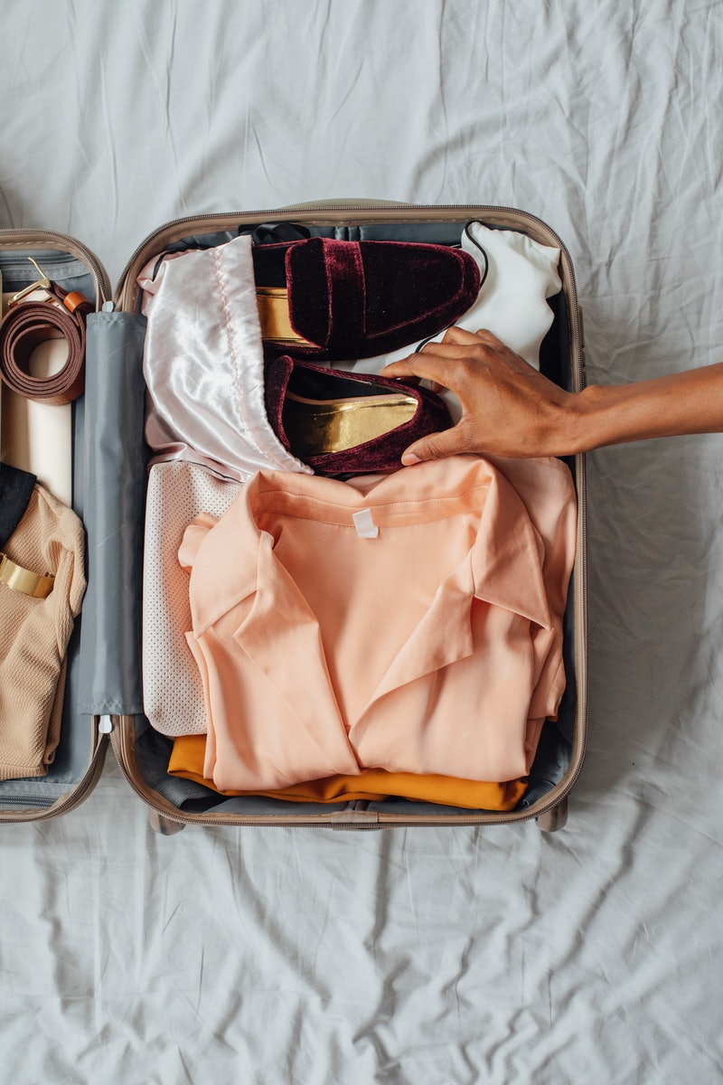 Hands of unrecognisable woman putting velvet loafers in her suitcase. Is it safe to travel once your...