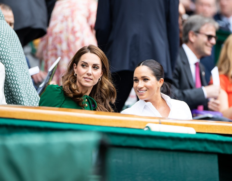 LONDON, ENGLAND - JULY 13: Catherine, Duchess of Cambridge talks with Meghan, Duchess of Sussex in the royal box before the start of the Women's Singles Final between Simona Halep of Romania and Serena Williams of USA (not pictured) at The Wimbledon Lawn Tennis Championship at the All England Lawn and Tennis Club at Wimbledon on July 13, 2019 in London, England. (Photo by Simon Bruty/Anychance/Getty Images)