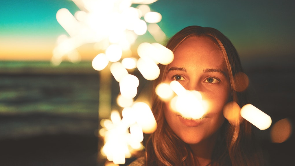 Shot of a young woman holding a sparkler at the beach at night