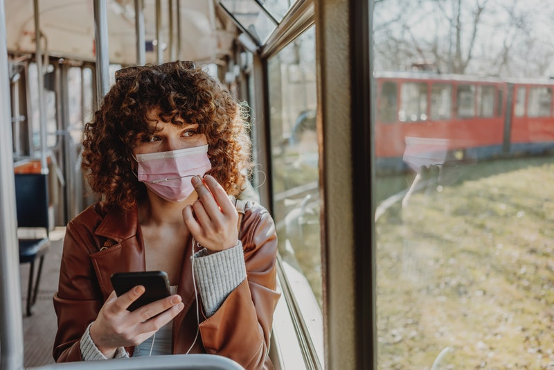 Young woman in public transportation during the pandemic. Safety apps for women for iPhone and Andro...