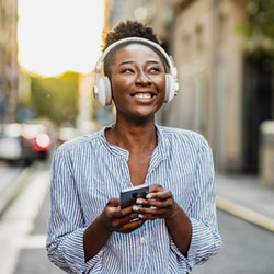 Young African American woman is in the city and using a mobile phone