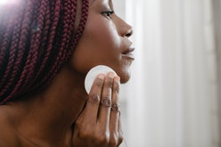 Beautiful African woman cleaning her face with cotton pad.