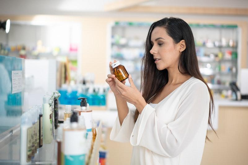 Woman choosing sunscreen lotion at the pharmacy