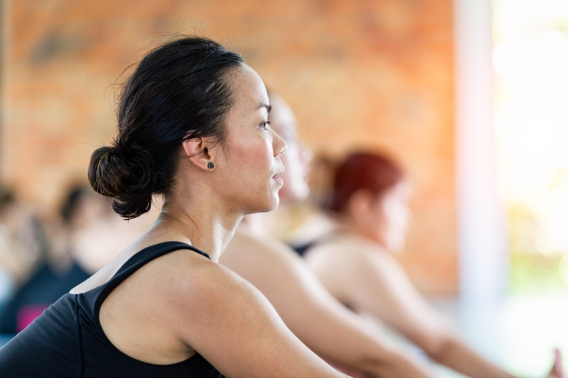 Fitness asian female group doing warm up yoga pose in row at the yoga class, Ubon Ratchathani, Thailand