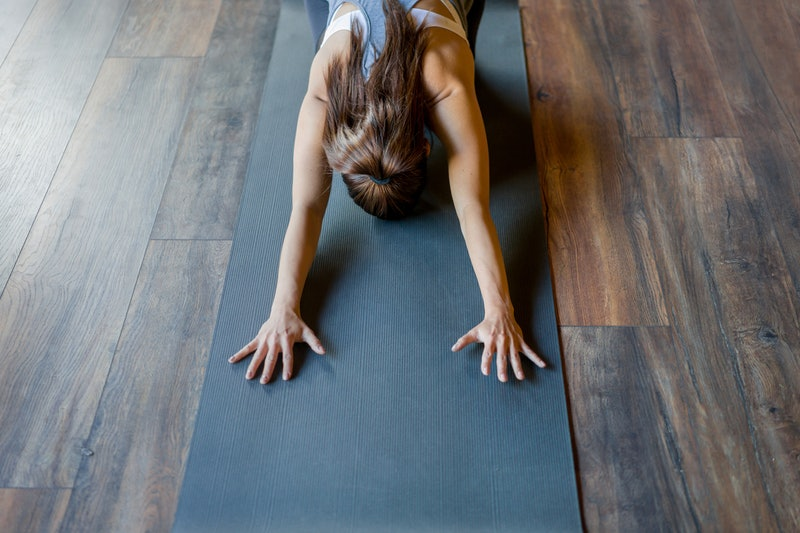 Young woman stretching her back while doing yoga at the gym. Here's why your muscles hurt when you're anxious.