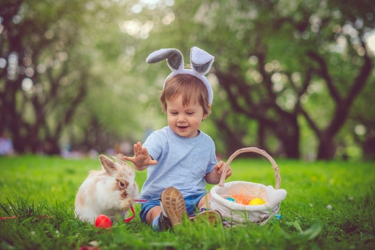 Happy child playing with bunny on Easter egg hunt in springtime