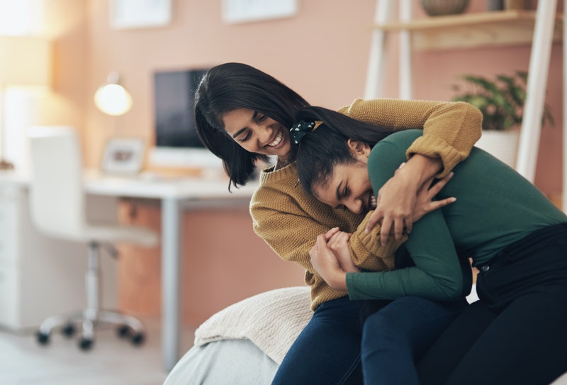 Shot of two happy young women sitting together at home post-COVID. Anxiety experts explain how to deal with quarantine-induced social anxiety.