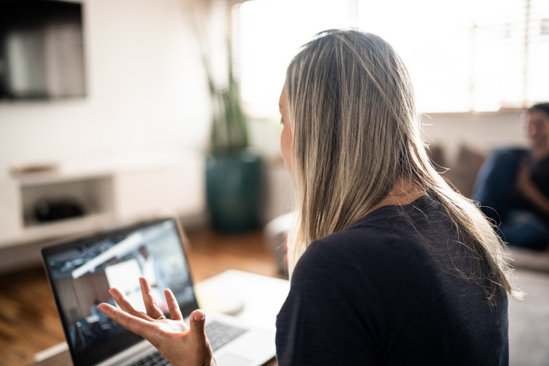 Rear view of a mature woman doing a business video call at home