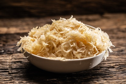 A bowl full of raw sauerkraut cabbage pickle on a rustic dark surface.