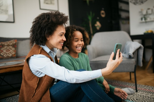 Happy African American family, single mother and her daughter at home, celebrating international women's day together, having fun, smiling and taking a selfie with a smart phone