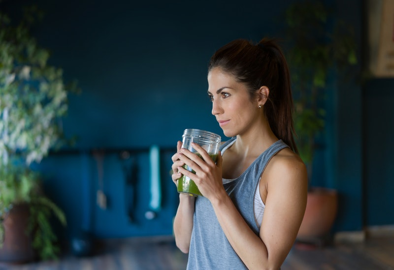 Portrait of an athletic Latin American woman drinking a detox smoothie at the gym - healthy lifestyle concepts