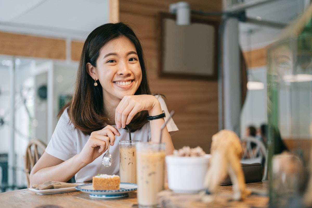 A happy woman enjoys a cake and iced latte at a coffee shop.