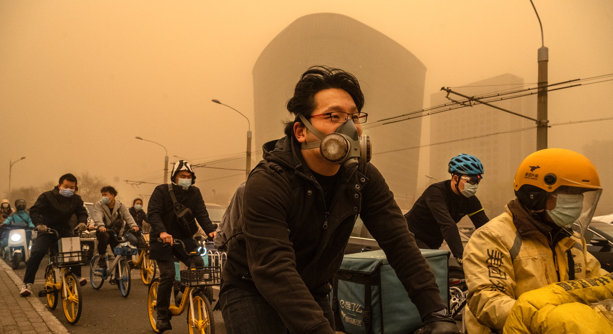BEIJING, CHINA - MARCH 15: People wear protective masks as they commute during a sandstorm on March 15, 2021 in Beijing, China. The Chinese capital and the northern parts of the country was hit with a sandstorm on Monday, sending air quality indexes of PM 2.5 and PM 10 ratings into the thousands and cancelling flights. (Photo by Kevin Frayer/Getty Images)