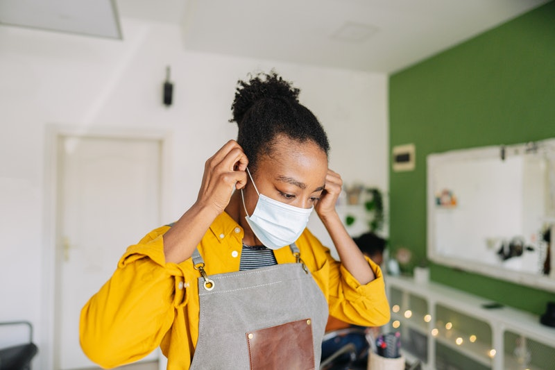Portrait of a young African American hairdresser, proud owner of a small business, wearing protective face mask due to coronavirus pandemic. Legal & psychological experts explain the definition of sexual harassment and how it's different from street harassment and sexual assault.