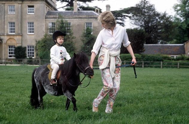 Princess Diana shows Prince William how to ride a pony.