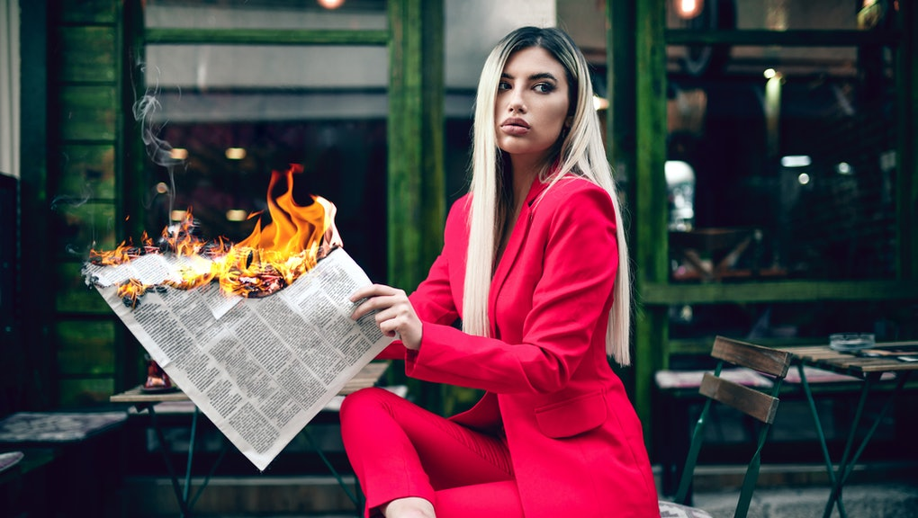 Elegant Female Reading Burning Newspaper