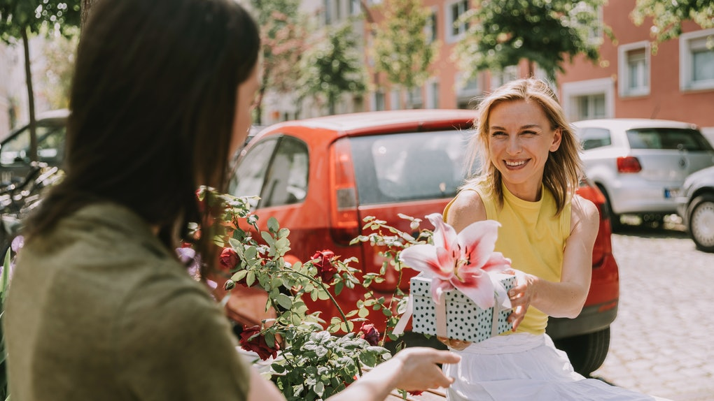 A young woman hands one of her bridesmaids a unique gift that they'll use and love.
