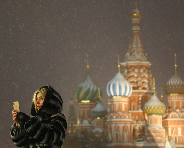 MOSCOW, RUSSIA - FEBRUARY 4, 2021: A woman stands in front of St Basil's Cathedral during a snowfall in Red Square. Valery Sharifulin/TASS (Photo by Valery Sharifulin\TASS via Getty Images)