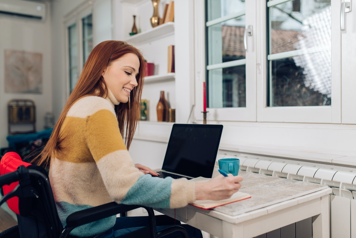 Young redhead woman in a wheelchair working online from home.