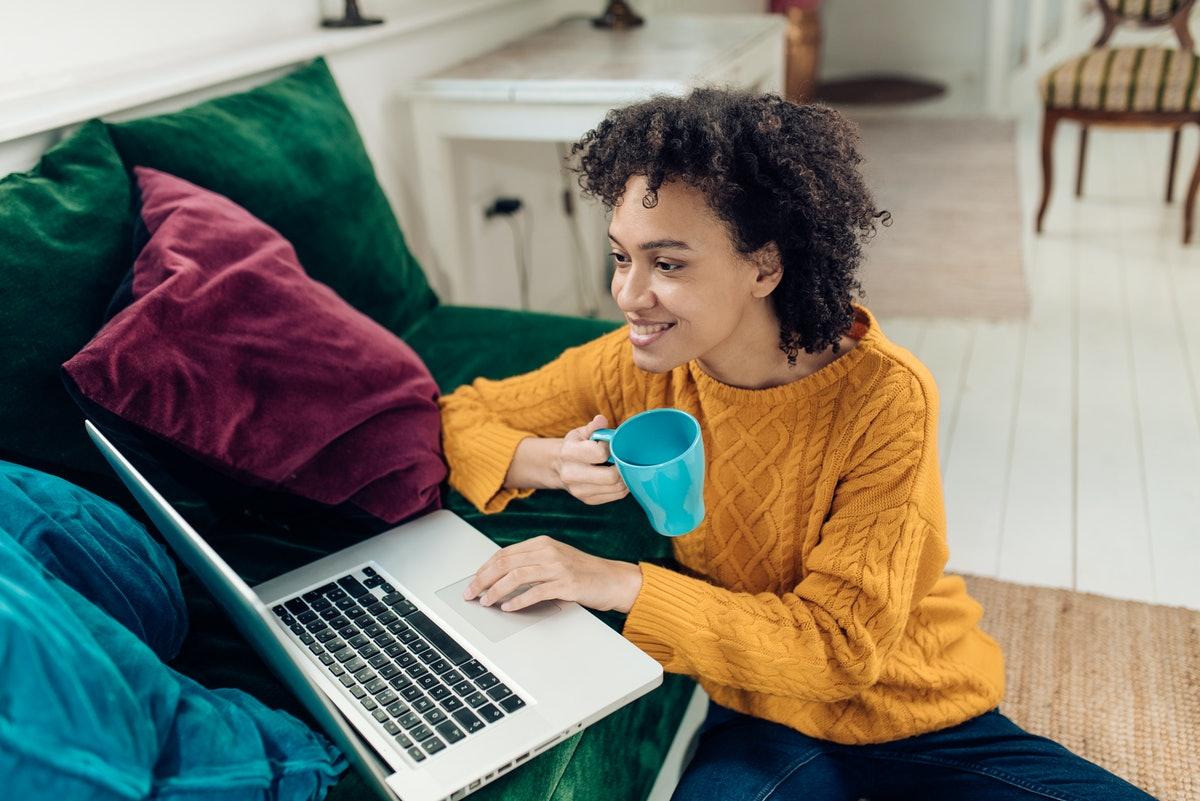 Young African-American woman working from her living room.