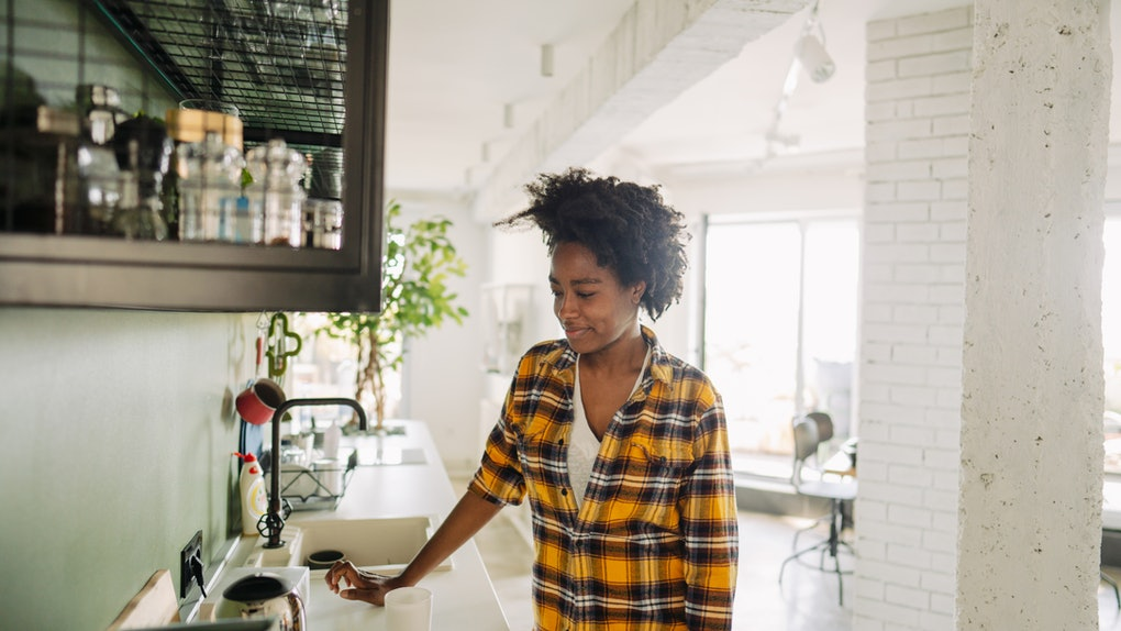 A woman makes coffee in her apartment in the morning.