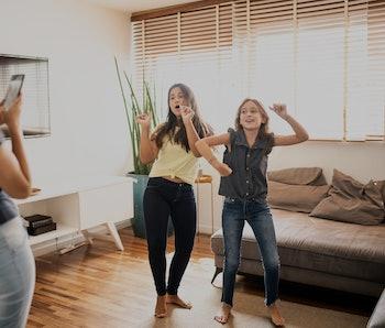 Mother filming teenager daughters dancing at home