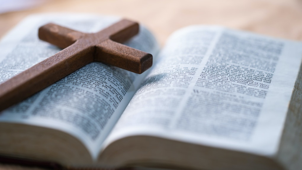 The cross is placed on the Bible.