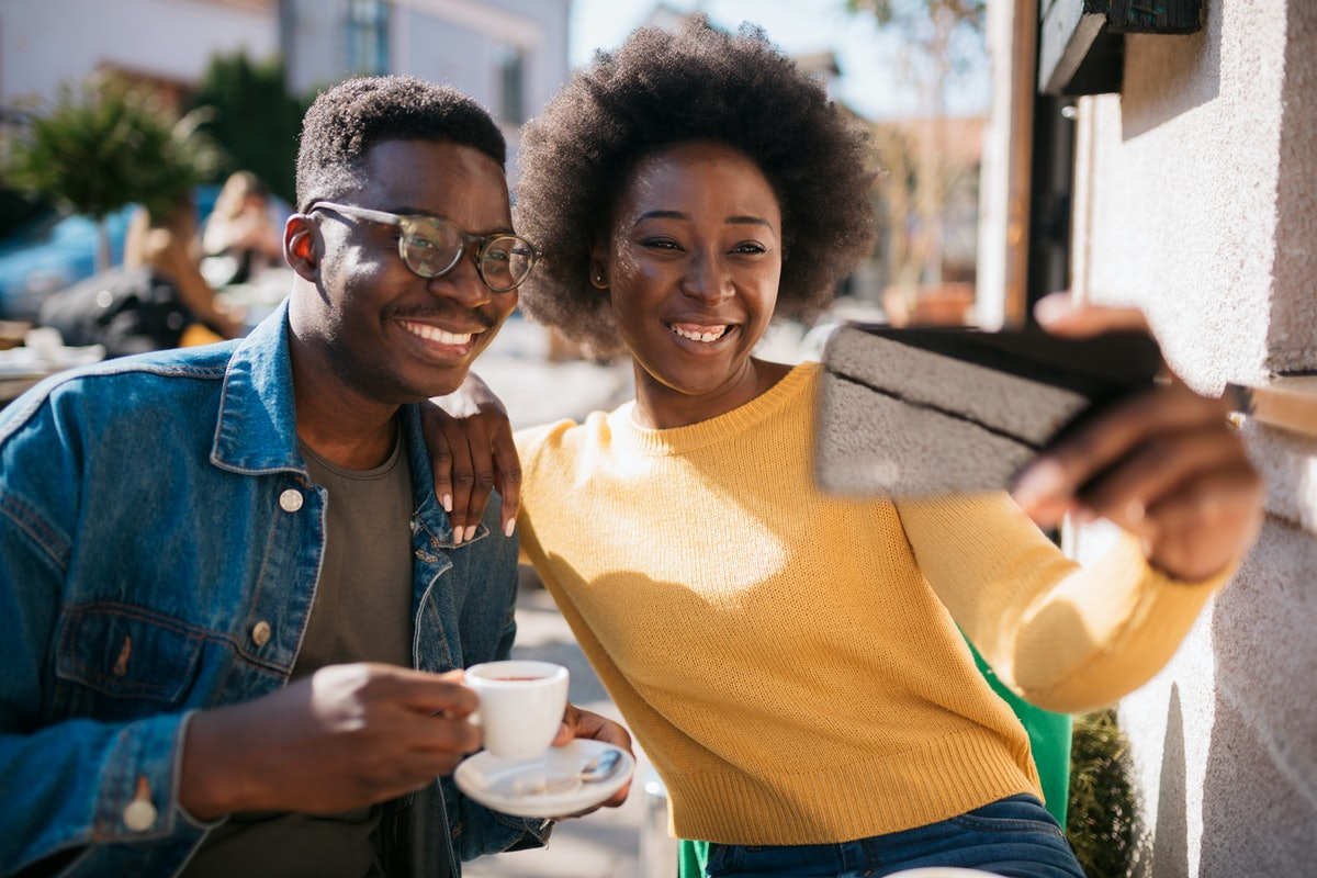 Happy smiling African American couple, sitting in a coffee shop, relaxing and enjoying their vacation and each other, taking a selfie together with a smart phone
