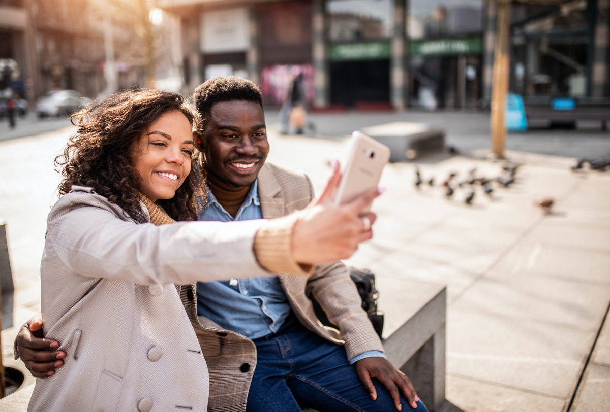 Happy young African American couple taking a photo together in the city.