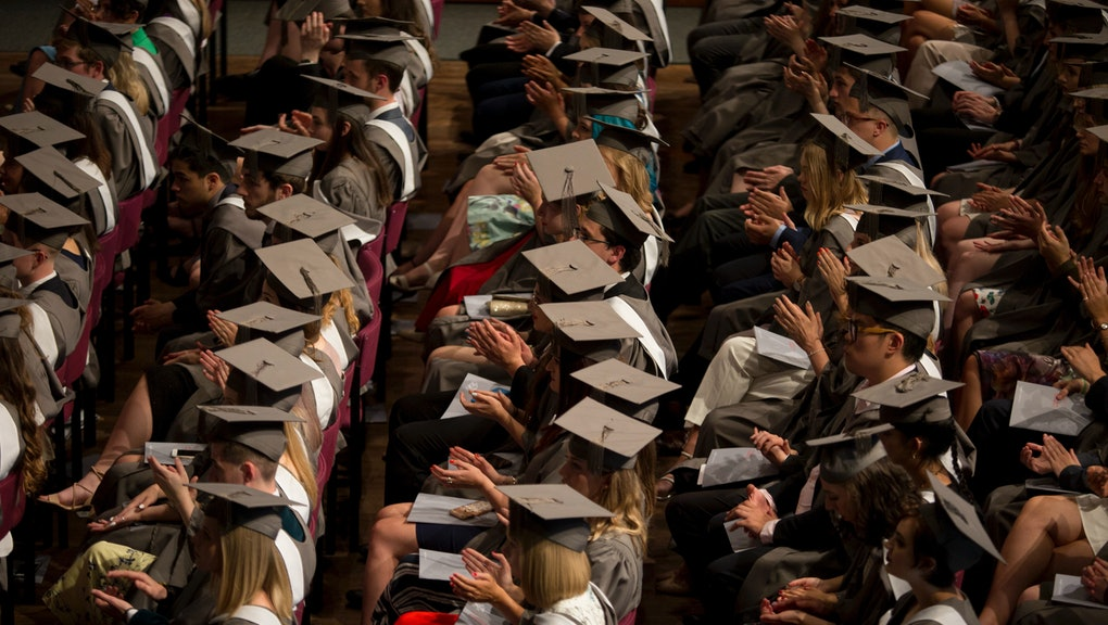 Young graduates wearing rented gowns and mortarboards applaud a speech in the central hall of their university during their graduation ceremony, on 13th July 2017, at the University of York, England. (Photo by Richard Baker / In Pictures via Getty Images Images)
